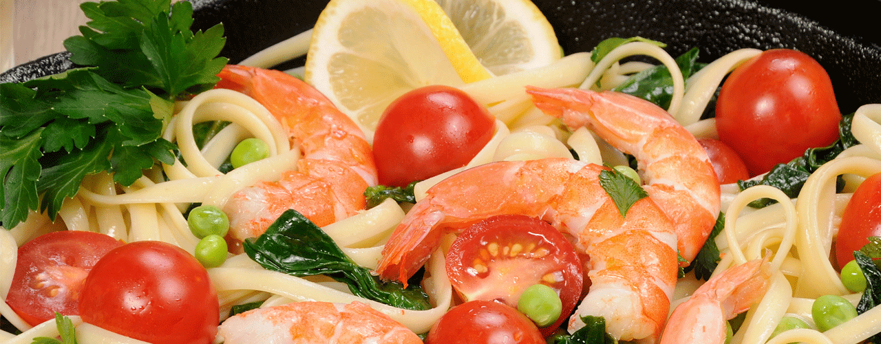 A bowl of pasta mixed with tomatoes, peas and shrimp.
