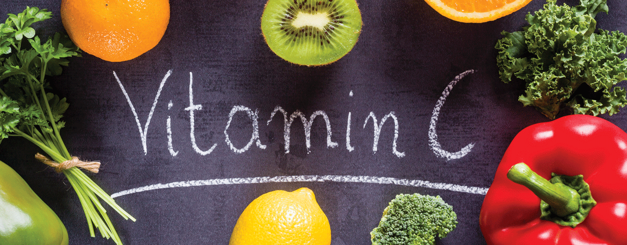 A top view of oranges, kiwi, tomato, broccoli, lemon, and red pepper next to text that says Vitamin C.