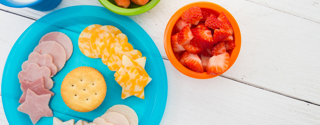 A top view of a plate with lunch meat cutouts, carrots in a bowl, and strawberries in bowl.