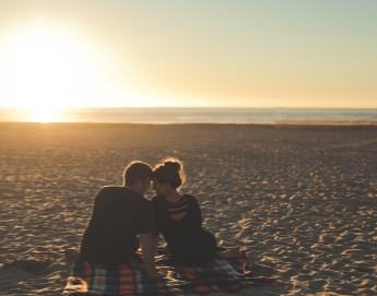 A couple snuggling on the beach watching the sunset.