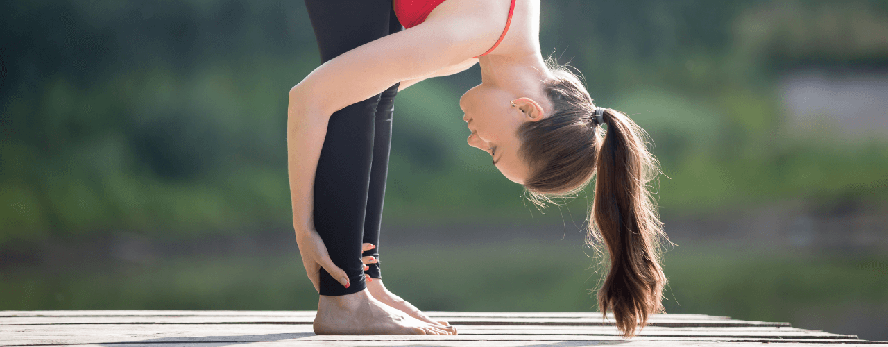 A young girl outside on a deck holding a yoga pose.