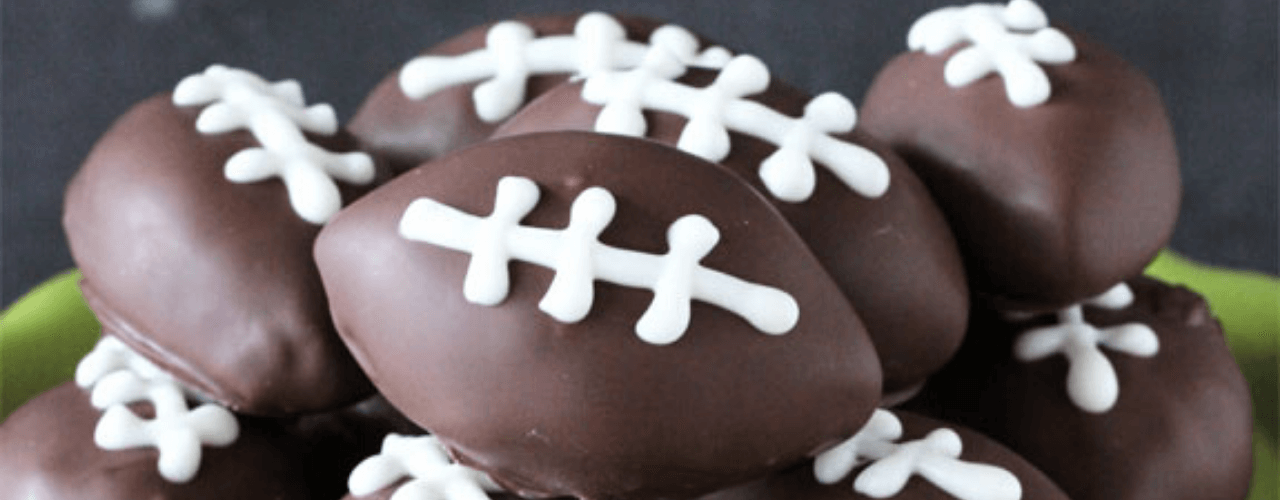 A plate full of chocolate covered treats in the shape of a football.