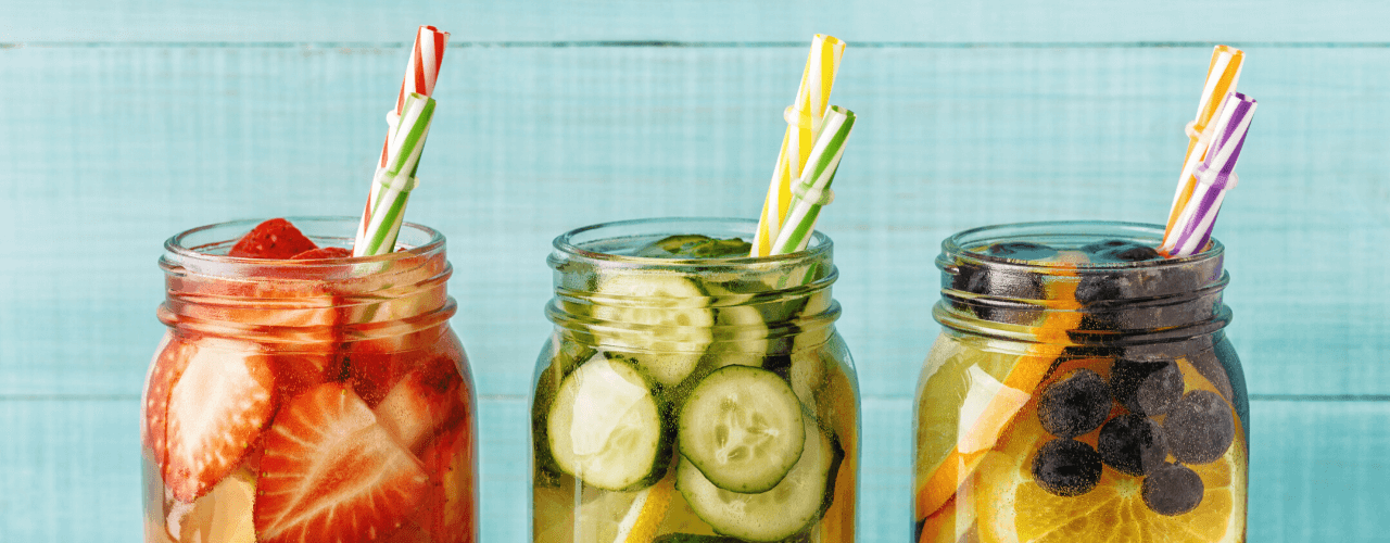 Mason jars filled with assorted fruits floating in water.