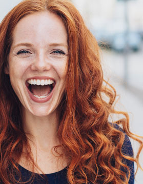 Woman with red hair smiling.