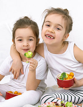 Two young sisters eating vegetables.