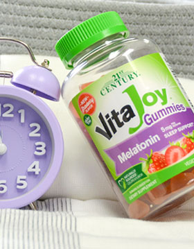 Clock next to Vijajoy Gummies bottle on a bed.